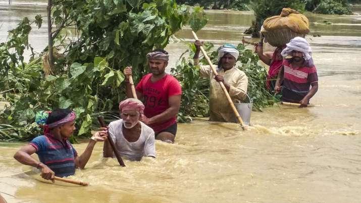 People cross a flooded street following incessant monsoon rainfall, at Madhubani district.