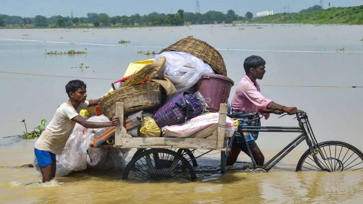 Flood-affected villagers transport their belongings to a safer place from their flooded village at Mithan Sharay in Muzaffarpur district.