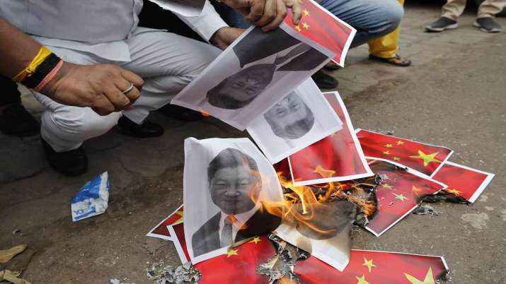 Indians burn photographs of Chinese President Xi Jinping during a protest against the Chinese govern