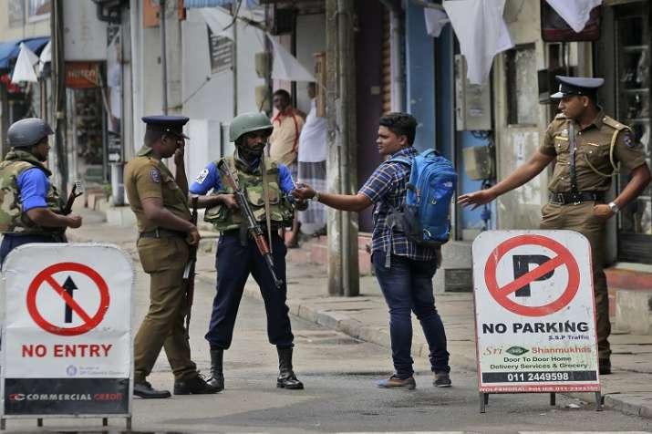 Sri Lankan policemen check the identity card of a person...- India TV