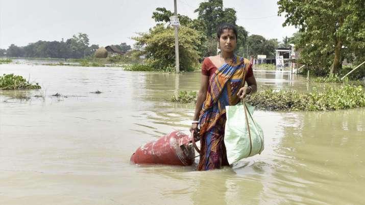 तस्वीर असम के मोरीगांव की हैै जहां  महिला बाढ़ के बीच घर के लिए सिलेंडर लेकर आ रही है।