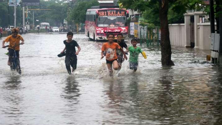 Children play at a waterogged road following heavy monsoon rain in Varanasi- India TV