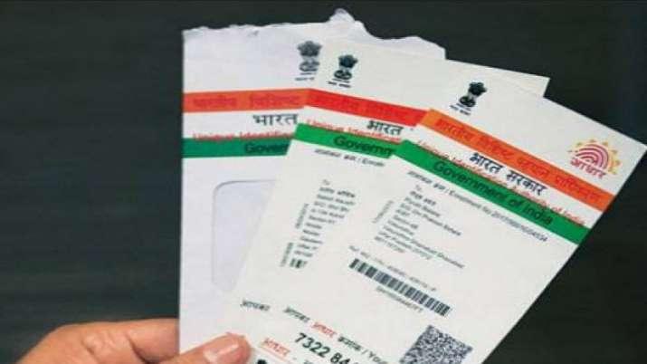 एक व्यक्ति आधार कार्ड की कुछ प्रतियां हाथ में पकड़़े़े हुुुुए। - India TV Paisa