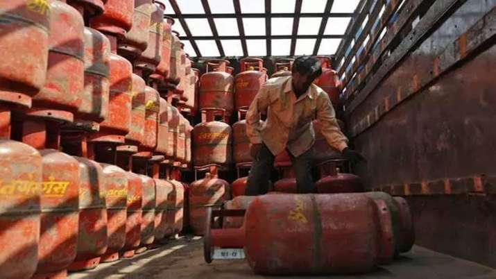 ट्रक से एलपीजी सिलेेंडर नीचे उतारता हुआ एक कर्मचारी। (चित्र प्रतीकात्मक)- India TV Paisa
