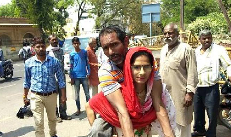 Woman in Mathura carries handicapped husband on shoulders to get disability certificate- India TV Hindi