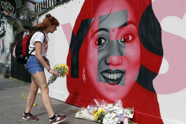 A woman places flowers by a mural showing Savita Halappanavar   AP Photo- India TV Hindi