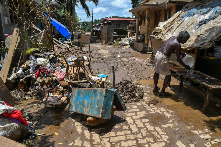 A man cleans up his house after flood water subsided, in...- India TV Hindi