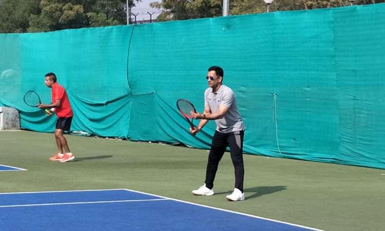 क्रिकेट का बल्ला नहीं टेनिस रैकेट लेकर मैदान पर उतरे एमएस धोनी, देखें तस्वीरें- India TV Hindi