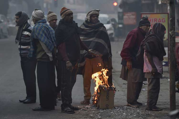 People gather around a makeshift bonfire to warm...- India TV Hindi