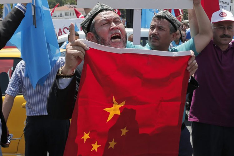 Uighurs living in Turkey and Turkish supporters, chant slogans as they hold a Chinese flag | AP File- India TV Hindi