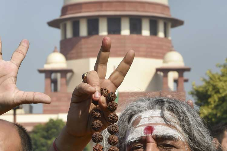 A sadhu flashes the victory sign at the Supreme Court...- India TV Hindi