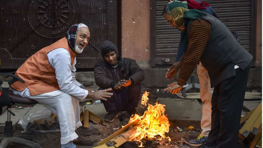 People warm themselves around a bonfire- India TV Hindi
