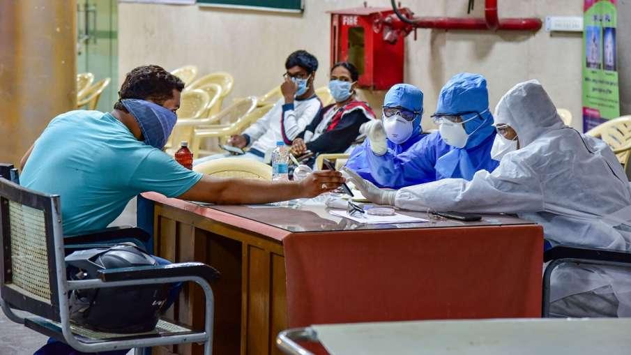 Medics interact with a patient at a help desk, set- up in view of coronavirus pandemic, at Gandhi Ho- India TV Hindi