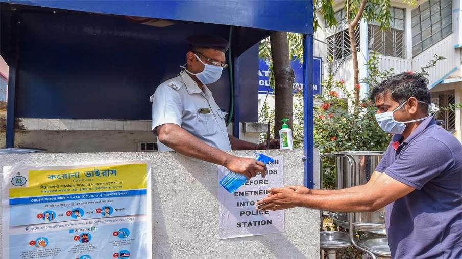 Kolkata: A police person provides hand sanitizer to a...- India TV Hindi