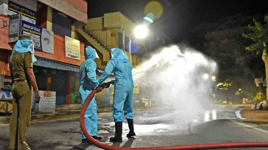 Health workers spray disinfectant on a street during the...- India TV Hindi