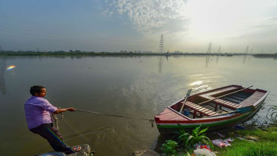 A man pulls his boat to anchor at the bank of swollen Yamuna River in New Delhi on Friday. The water- India TV Hindi
