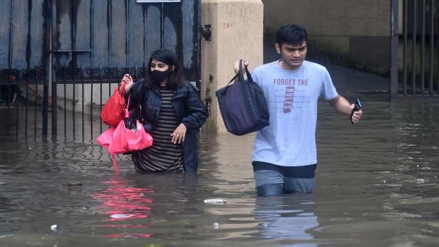 People make their way through the waterlogged streets at Kings Circle in Mumbai.- India TV Hindi